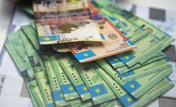 Купюры тенге в отделении банка Eurasian Bank в Алма-Ате. 15 января 2015 года. Богатый нефтью Казахстан в среднесрочной перспективе обещает удержать национальную валюту в коридоре 170-188 тенге за $1 при цене на нефть не менее $50 за баррель, перейти к инфляционному таргетированию и к 2020 году снизить рост цен в стране до 3-4 процентов. REUTERS/Shamil Zhumatov