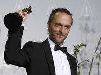"""Emmanuel Lubezki poses with his award for best cinematography for his film """"Gravity"""" at the 86th Academy Awards in Hollywood, California March 2, 2014  REUTERS/ Mario Anzuoni"""