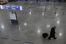 Un pasajero camina en el aeropuerto Eleftherios Venizelos de Atenas. 6 de noviembre de 2012. Grecia planea revisar el acuerdo de 1.200 millones de euros por el que se otorgó a la operadora aeroportuaria alemana Fraport  la gestión de 14 aeropuertos regionales en uno de los mayores acuerdos de privatización desde que comenzó la crisis de deuda en 2009, dijo el sábado el ministro de Coordinación del Gobierno, Alekos Flabouraris. REUTERS/John Kolesidis
