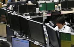 Сотрудник трейдинговой компании в Токио. 31 октября 2014 года. Азиатские фондовые рынки выросли вслед за рынками США и накануне очередных переговоров о кредитовании Греции. REUTERS/Toru Hanai