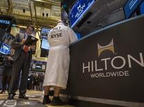 Specialist Trader John O'Hara (R) wears a Hilton branded bathrobe to celebrate Hilton's IPO, while working at his post on the floor of the New York Stock Exchange, December 13, 2013. REUTERS/Brendan McDermid