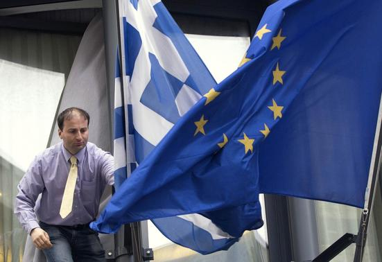 A man adjusts a Greek (L) and a European flag outside the Greek embassy in Brussels February 19, 2015. REUTERS-Yves Herman
