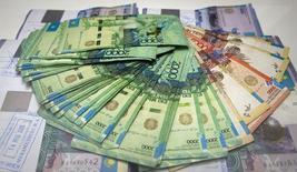 Купюры тенге в отделении банка Eurasian Bank в Алма-Ате. 15 января 2015 года. Мажилис, нижняя палата парламента Казахстана, в среду одобрил поправки в бюджет 2015 года, предполагающие сокращение расходов, доходов, увеличение дефицита; параметры бюджета сверстаны исходя из мировой цены на нефть в $50 против прежнего прогноза $80 за баррель марки Brent. REUTERS/Shamil Zhumatov