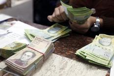 Una cajera cuenta bolívares en una casa de cambios en Caracas, feb 24 2015. El precio del dólar en el mercado paralelo de Venezuela siguió el jueves su tendencia alcista y cotizaba en 214,18 bolívares tras cruzar, un día antes, la barrera psicológica de los 200 bolívares, a pesar de los esfuerzos del gobierno socialista de Nicolás Maduro por frenar el repunte en ese mercado. REUTERS/Carlos Garcia Rawlins