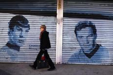 A pedestrian walks past pictures of original Star Trek actors Leonard Nimoy and William Shatner painted onto store front security gates on Hollywood Boulevard in Hollywood, California February 22, 2012.   REUTERS/Mike Blake