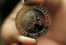 Assistente da National Portrait Gallery, em Londres, segurando a moeda de 2 libras com o novo retrado da Rainha Elizabeth.  02/03/2015  REUTERS/Suzanne Plunkett