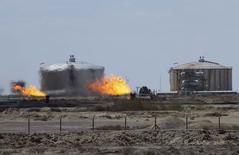 Факелы попутного газа на нефтепроводе с месторождения Зубайр в Басре. 5 марта 2015 года. Цены на нефть растут на фоне усиления боев в Ираке и Ливии, а трейдеры ждут еженедельных данных о числе работающих буровых установок в США и результатов переговоров о ядерной программе Ирана. REUTERS/Essam Al-Sudani