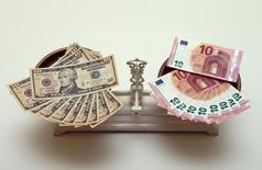 Банкноты доллара США и евро на чашах весов. Вена, 11 марта 2015 года. Евро вновь упал до 12-летнего минимума к доллару за счет начала количественного смягчения Европейского центробанка. REUTERS/Heinz-Peter Bader