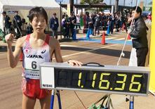 Japan's Yusuke Suzuki poses next to a electric time board showing his record after breaking the 20-kilometer race walk world record at the IAAF Race Walking Challenge, in Nomi, central Japan, in this photo taken by Kyodo March 15, 2015. Mandatory credit REUTERS/Kyodo