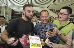 "BuzzFeed writer Matt Stopera (L) of the U.S. reacts as he looks at a mobile phone held by ""Brother Orange"" (C) of China, at an airport in Jieyang, Guangdong province March 17, 2015.  REUTERS/Stringer"