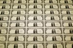 Una plantilla de billetes de un dólar durante su producción en la Casa de la Moneda de Estados Unidos en Washington, nov 14 2014. El dólar retrocedía el miércoles contra la mayoría de las principales divisas porque los inversores continuaban recortando sus sobredimensionadas posiciones en moneda estadounidense, antes del comunicado de la Reserva Federal tras su reunión de política monetaria.   REUTERS/Gary Cameron