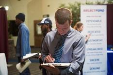 Nikolai Jones rellena una aplicación en una feria laboral en Williston, EEUU, mar 11 2015. El número de estadounidenses que solicitó beneficios por desempleo por primera vez subió marginalmente la semana pasada, lo que indica que el mercado laboral se mantiene sólido pese a la desaceleración del crecimiento económico. REUTERS/Andrew Cullen