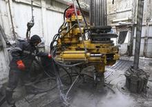 Нефтяник на Сузунском месторождении Роснефти в Красноярской области. 26 марта 2015 года. Цены на нефть упали более чем на $1 за баррель после резкого роста в четверг, так как инвесторы меньше беспокоятся, что авианалеты Саудовской Аравии в Йемене вызовут перебои в поставках нефти. REUTERS/Sergei Karpukhin