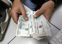 Сотрудник частной красноярской компании считает рубли. 17 декабря 2014 года. Рубль растет в четверг на фоне негативной динамики американской валюты на мировых рынках и вчерашнего нефтяного ралли в условиях тонкого малоликвидного рынка начала календарного месяца, а также перед западной Пасхой и важной пятничной публикацией о занятости и безработице в США. REUTERS/Ilya Naymushin