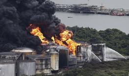 Humo y llamas salen de tanques en las instalaciones de almacenamiento de combustibles de Ultracargo en el puerto de Santos. 3 de abril de 2015. Un incendio de instalaciones de almacenamiento de combustibles en el puerto brasileño de Santos, el mayor del país, se propagó el sábado a otro tanque a pesar de los esfuerzos de los bomberos durante los últimos tres días para contener las llamas. REUTERS/Nacho Doce     - RTR4W13K
