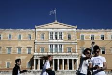 En la imagen, varias personas pasan junto al Parlamento griego en Atenas, el 6 de abril de 2015.  Legisladores griegos votaron el martes a favor de la creación de un comité que examine las circunstancias en las que Atenas acordó recibir rescates por un total de 240.000 millones de euros (260.000 millones de dólares) con la Unión Europea y el Fondo Monetario Internacional. REUTERS/Alkis Konstantinidis