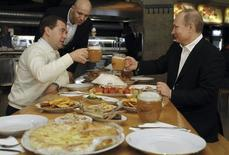 Russian President Dmitry Medvedev (L) and Prime Minister and President-elect Vladimir Putin toast with beer during a visit to a self-service restaurant after taking part in a march to celebrate International Workers' Day, or Labour Day, in Moscow May 1, 2012. REUTERS/Dmitry Astakhov/RIA Novosti/Kremlin