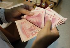 El gobernador del banco central de China, Zhou Xiaochuan, dijo que Pekín aceleraría las reformas a la moneda del país para impulsar la inclusión del yuan en la canasta de monedas del FMI, conocida como Derechos Especiales de Giro (SDR), informó el sábado la agencia oficial de noticias Xinhua. En la imagen, una mujer cuenta billetes de yuan en un mercado de Pekín el 1 de julio de 2013.  REUTERS/Jason Lee