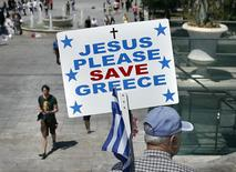 A man holding a Greek national flag and a placard walks in Constitution (Syntagma) Square in Athens May 4, 2015. REUTERS/Alkis Konstantinidis