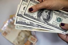 Mulher segura notas de dólares em cima de notas de real no Rio de Janeiro. 31/03/2015 REUTERS/Sergio Moraes