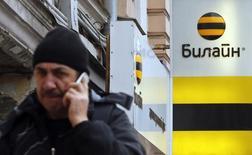 Мужчина говорит по телефону у салона связи Билайн в Москве. 12 ноября 2014 года. Чистая прибыль телекоммуникационной группы Вымпелком в первом квартале 2015 года увеличилась до $184 миллионов с $38 миллионов, сообщила компания в среду. REUTERS/Maxim Shemetov