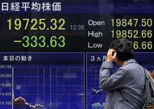 Un peatón se rasca la cabeza y mira un tablero electrónico que muestra el índice Nikkei de la Bolsa de Tokyo, en Tokyo, Japón, 30 de abril de 2015. Las bolsas de Asia caían el lunes y el dólar se mantenía cerca de un mínimo de cuatro meses frente a una canasta de monedas importantes después de que unos datos débiles plantearon dudas sobre si la economía de Estados Unidos ha estado creciendo en momentos en que los precios de las acciones en ese país operan en máximos históricos. REUTERS/Yuya Shino
