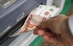 Мужчина забирает деньги из банкомата в Москве. 2 сентября 2014 года. Рубль дешевеет утром четверга, поскольку заявленная сегодня  Центробанком возможность изменения объемов интервенций была воспринята рынком как риск увеличения текущих ежедневных покупок валюты регулятором. REUTERS/Maxim Zmeyev