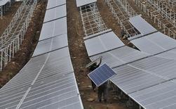 Trabajadores llevando paneles solares mientras trabajan en una planta de energía solar, la cual está en construcción, en una colina en Wuhu, provincia de Anhui, 16 de septiembre de 2014. La actividad manufacturera de China se redujo por tercer mes en mayo y la producción se contrajo a su mayor tasa en poco más de un año, mostró un sondeo privado, lo que indica una persistente debilidad en la segunda mayor economía mundial que requiere de un mayor respaldo de política. REUTERS/Stringer