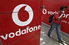 Un hombre habla por celular mientras camina junto a logos de Vodafone pintados en paredes en Kolkata, 20 de mayo de 2014. El principal índice británico de acciones tocó el viernes máximos de 10 días, impulsado por los títulos del operador de telefonía móvil Vodafone, que alcanzaron máximos de 14 años por comentarios sobre potenciales fusiones. REUTERS/Rupak De Chowdhuri