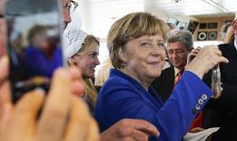 Una persona le toma una fotografía a Angela Merkel, en Ruegen, 26 de mayo de 2015. La canciller de Alemania, Angela Merkel, lideró por quinto año consecutivo la lista de las 100 mujeres más poderosas del mundo que elabora la revista Forbes, relegando al segundo lugar a la precandidata a la presidencia de Estados Unidos Hilary Clinton. REUTERS/Fabrizio Bensch/Files