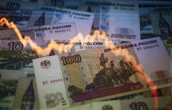 График колебаний курса рубля к доллару на фоне рублевых купюр в Варшаве 7 ноября 2014 года. Доллар дорожает на процент с четвертью к российской валюте, превысив отметку в 57 рублей впервые за два месяца, следуя в русле повсеместного спроса на американскую валюту после сильной трудовой статистики США; против рубля также текущее падение нефти на полуторамесячные минимумы и уход в безопасные активы на выходные дни в условиях неопределенной ситуации на востоке Украины. REUTERS/Kacper Pempel