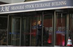 Человек выходит из здания фондовой биржи в Шанхае 17 ноября 2014 года. Азиатские фондовые рынки снизились во вторник на фоне опасений за Грецию и ожиданий первого почти за 10 лет повышения процентных ставок ФРС в сентябре. REUTERS/Carlos Barria