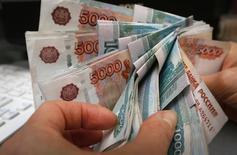 Сотрудник магазина пересчитывает рублевые купюры в Красноярске 26 декабря 2014 года. Рубль завершает торги понедельника в плюсе, продолжив укрепление с сессионных  минимумов после решения Центробанка снизить ставку в соответствии с ожиданиями рынка, несмотря на падение цен нефти и рост доллара на глобальном рынке. REUTERS/Ilya Naymushin