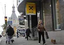 Люди проходят мимо отделения Райффайзен банка в Санкт-Петербурге 25 сентября 2014 года. Австрийский банк Raiffeisen Bank International (RBI) рассчитывает остаться прибыльным в России в этом году, несмотря на трудные условия для ведения бизнеса, сказал исполнительный директор Карл Севельда на встрече с акционерами банка. REUTERS/Alexander Demianchuk