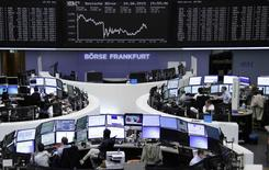 Traders are pictured at their desks in front of the DAX board at the Frankfurt stock exchange June 24, 2015.     REUTERS/Remote/Staff