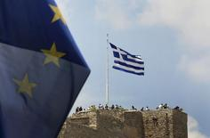 Флаги Греции и ЕС в афинском Акрополе. 26 июня 2015 года. Еврозона может помочь Греции выплатить долги в ближайшие месяцы посредством денег, выделенных в рамках действующей программы помощи, если эта программа будет продлена на пять месяцев, до ноября, говорится в документе, подготовленном для заседания министров финансов еврозоны. REUTERS/Yannis Behrakis