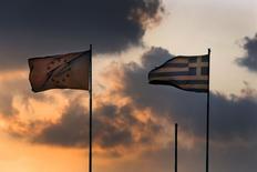Una bandera de la Unión Europea junto a una de Grecia, ondean sobre el Ministerio de Finanzas durante la puesta de sol, en Atenas, Grecia, 5 de junio de 2015. La confianza en la economía de la zona euro bajó en junio tras un enérgico comienzo de año, en una señal temprana de que la amenaza de cesación de pagos en Grecia pueda estar empezando a empeorar la confianza económica en el bloque. REUTERS/Yannis Behrakis