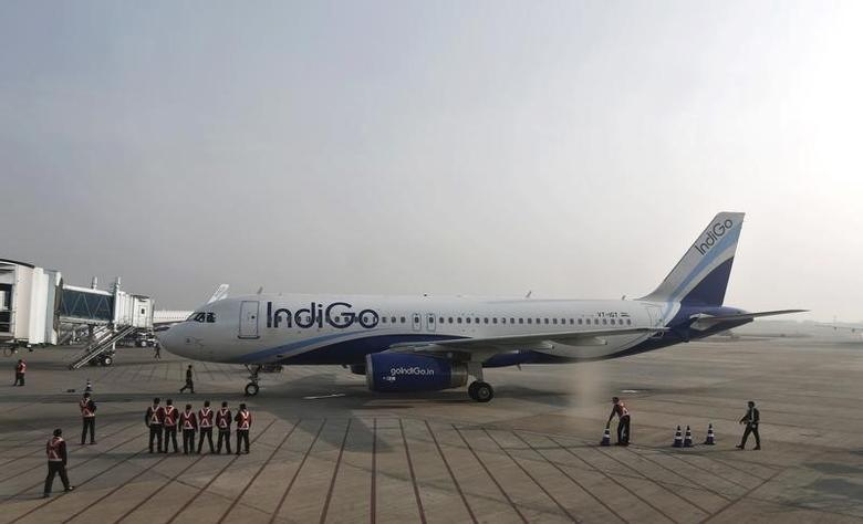 Indigo Airlines' ground staff stand next to an aircraft after it arrived at the Srinagar airport November 21, 2014. REUTERS/Adnan Abidi/Files
