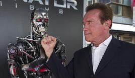 """Cast member Arnold Schwarzenegger poses by a Terminator replica at the premiere of """"Terminator Genisys"""" in Hollywood, California June 28, 2015.  REUTERS/Mario Anzuoni"""