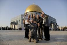 Palestinian Hussam Abu Daba'a (C), 55, from the West Bank city of Hebron, takes a selfie photo with friends and relatives in front of the Dome of the Rock on the compound known to Muslims as Noble Sanctuary and to Jews as Temple Mount, in Jerusalem's Old City, during the holy month of Ramadan, July 1, 2015.  REUTERS/Ammar Awad