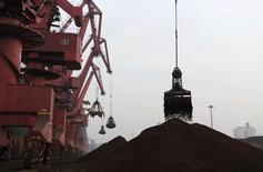 Cranes unload iron ore from a ship at a port in Rizhao, Shandong province February 7, 2015. REUTERS/China Daily