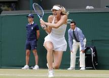 Maria Sharapova of Russia hits a shot during her match against Zarina Diyas of Kazakhstan at the Wimbledon Tennis Championships in London, July 6, 2015.                   REUTERS/Suzanne Plunkett