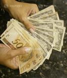Mulher em troca reais por dólares em uma casa de câmbio no Rio de Janeiro 7/05/ 2004.  REUTERS/Bruno Domingos