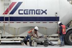 Trabajadores frente a un camión en una planta de concreto de la cementera mexicana CEMEX, en Monterrey, 24 de febrero de 2015. La empresa mexicana Cemex, una de las mayores cementeras del mundo, reportó el miércoles un alza del 50 por ciento en su utilidad neta del segundo trimestre, gracias a eficiencias y menores gastos financieros que compensaron una caída en sus ventas. REUTERS/Daniel Becerril