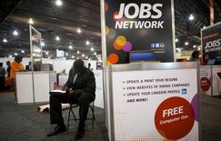 Una persona buscando trabajo completa un formulario en una feria de empleos en Filadelfia, 25 de julio de 2013. El número de estadounidenses que presentaron nuevas solicitudes de subsidios por desempleo cayó la semana pasada a su nivel más bajo en más de 41 años y medio, lo que sugiere que el mercado laboral mantuvo un ritmo sólido de creación de puestos de trabajo en julio. REUTERS/Mark Makela