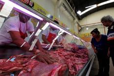 Unos clientes observan unos cortes de carne vacuna en el Mercado Argentino de Buenos Aires, abr 22 2013. Argentina dijo que la Organización Mundial de Comercio se pronunció el viernes a su favor en el conflicto que mantenía con Estados Unidos por una prohibición impuesta por ese país a las importaciones de carne bovina argentina.    REUTERS/Marcos Brindicci