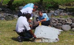 """Французские жандармы изучают обломок самолета, найденный на пляже на острове Реюньон. 29 июля 2015 года. Малайзия """"почти уверена"""", что обнаруженный на острове Реюньон в Индийском океане обломок самолета принадлежит """"боингу 777"""", пропавшему в марте прошлого года по пути из Куала-Лумпура в Пекин, сообщил чиновник Минтранса. REUTERS/Zinfos974/Prisca Bigot"""