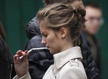 Студентка прикуривает на улице в Москве. 16 октября 2012 года. Одна из крупнейших табачных компаний в мире Japan Tobacco Inc сообщила в пятницу, что закроет фабрику Лиггетт-Дукат в Москве до середины 2016 года в связи с серьезным сокращением табачного рынка в России. REUTERS/Maxim Shemetov