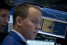 Un operador en la bolsa de Wall Street en Nueva York, jul 28 2015. Las acciones mostraban ligeras subidas el viernes cerca del mediodía en la bolsa de Nueva York, después de un dato históricamente bajo de crecimiento salarial en Estados Unidos que dio peso a especulaciones de que la Reserva Federal podría postergar un alza de las tasas de interés. REUTERS/Brendan McDermid