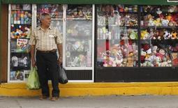 Un hombre lleva bolsas de compras frente a una tienda en Macas, Ecuador, 5 de noviembre de 2014. La tasa anual de inflación en Ecuador se aceleró levemente a 4,36 por ciento en los últimos 12 meses hasta julio frente a igual periodo previo, informó el jueves la agencia oficial de estadística. REUTERS/Guillermo Granja